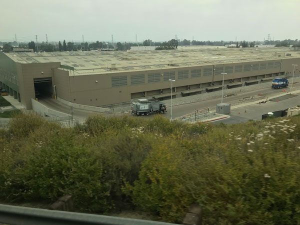 Nearly aerial view of a humongous boxy warehouse-like plant at the foot of Puente Hills.